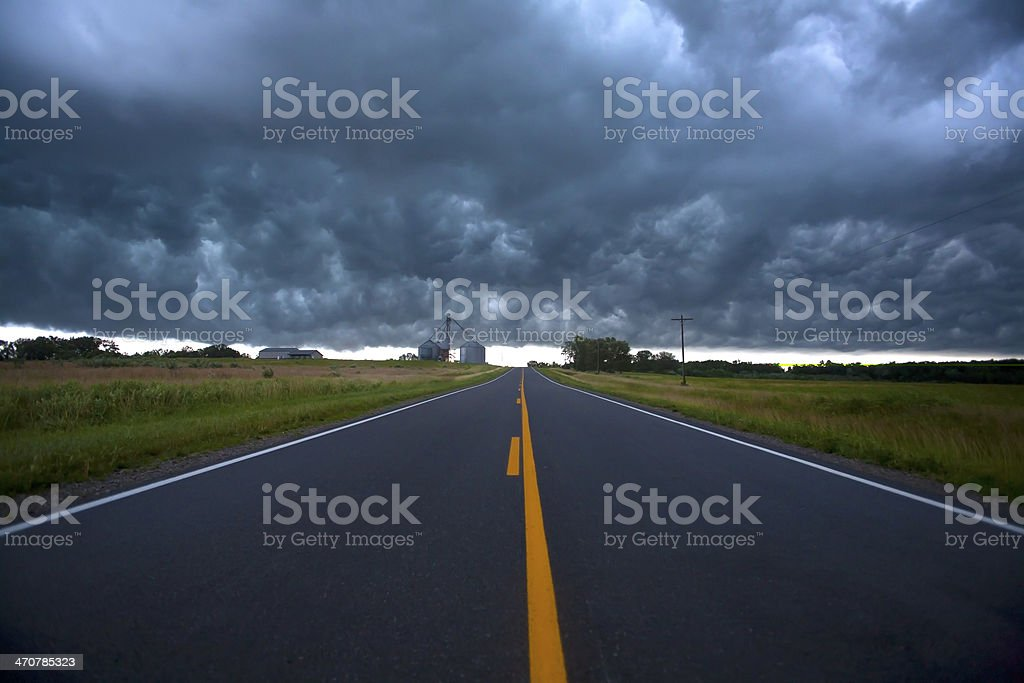 Dark storm clouds over road and farm royalty-free stock photo
