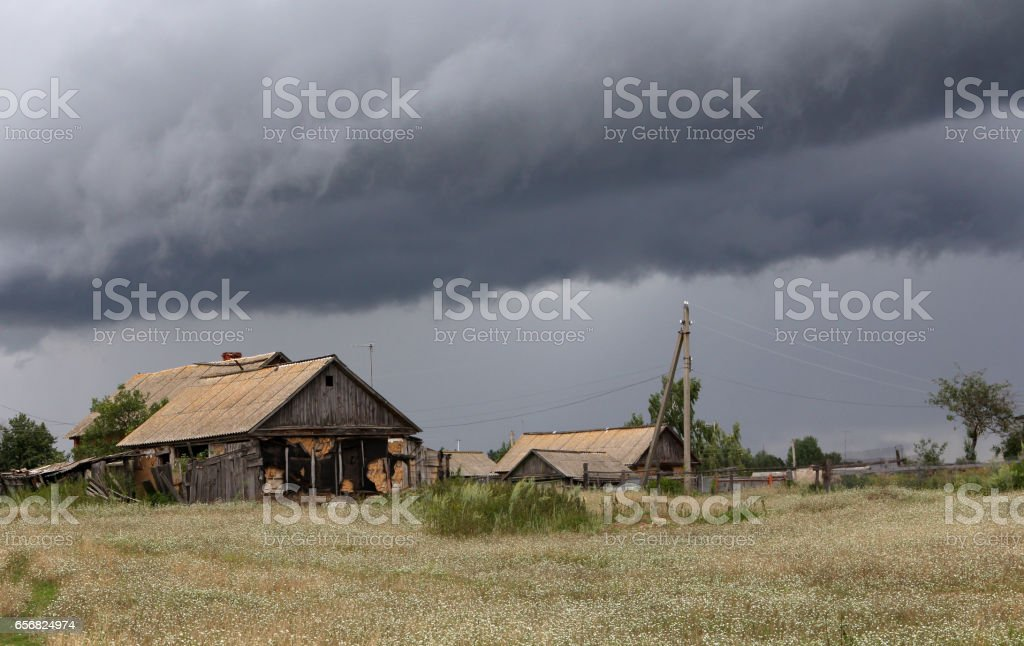 Dark storm clouds over the farmhouses stock photo