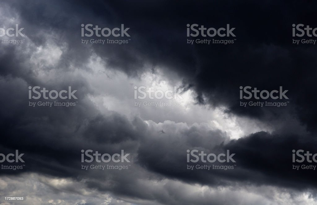 Dark storm clouds with sunlight poking through royalty-free stock photo