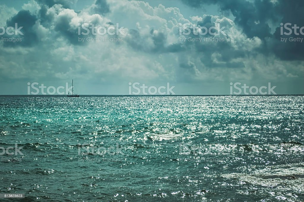 Dark stormy clouds and lighted sea stock photo