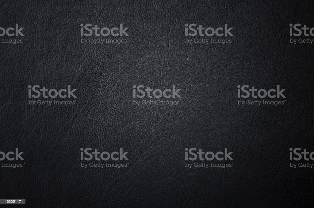 A dark texted background of black leather stock photo