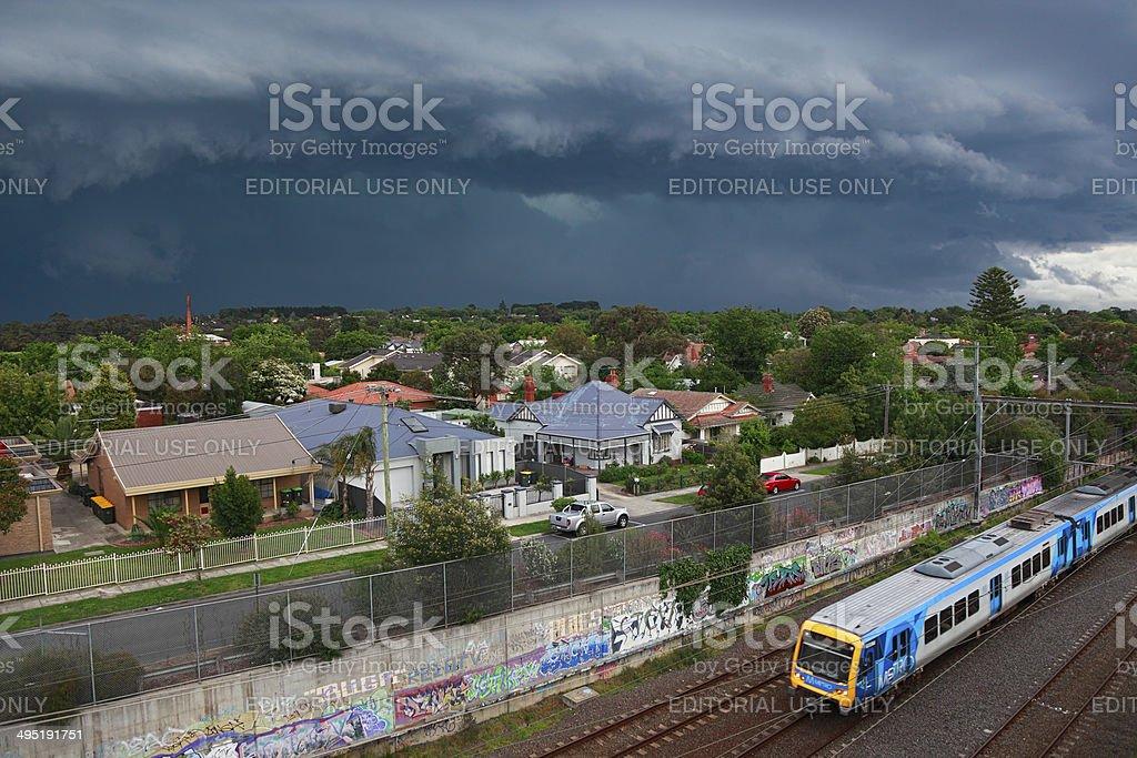 Dark, threatening storm looms over suburbs with metro train stock photo