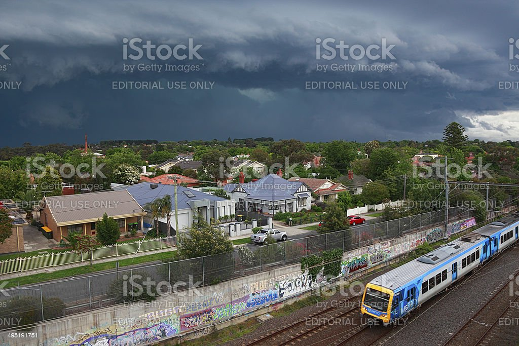 Dark, threatening storm looms over suburbs with metro train stock photo
