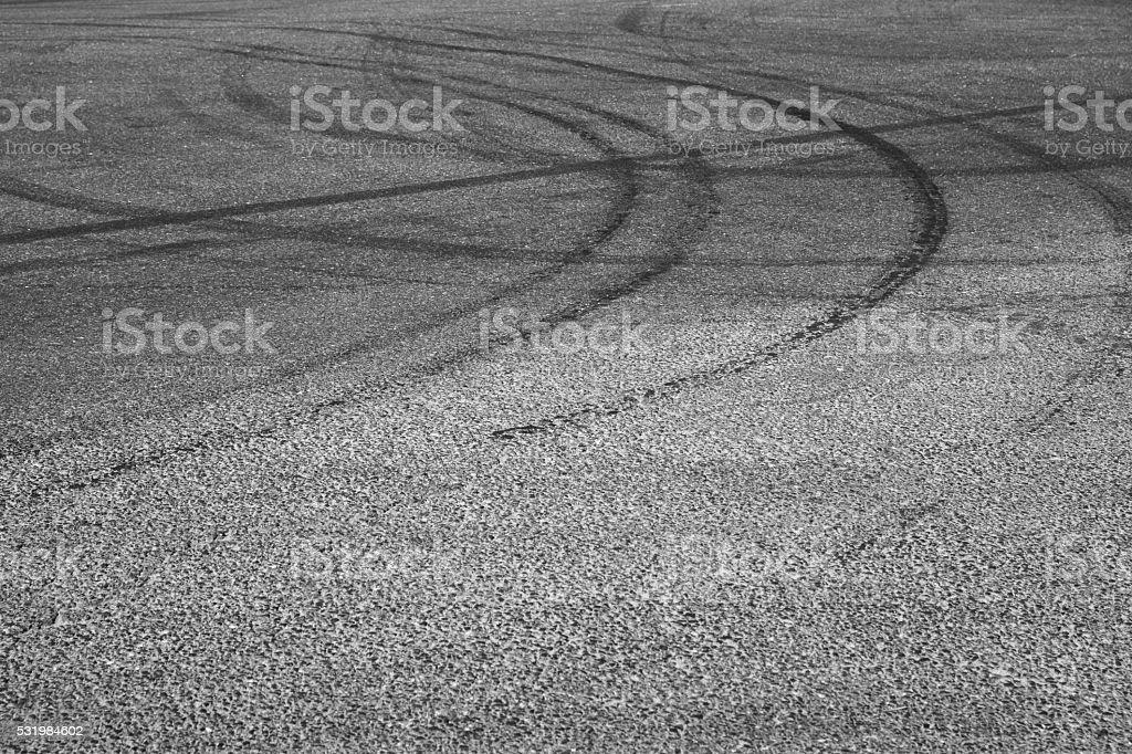 Dark tire tracks on gray asphalt road stock photo