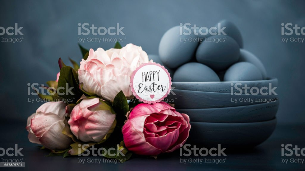 Dark toned Easter still life with peonies and hand painted ombre eggs stock photo