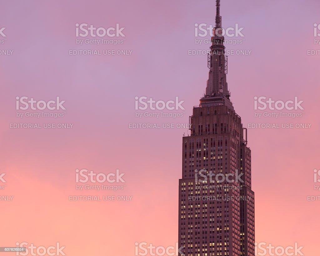 Dark top of Empire State Building, bright pink-orange sunset sky stock photo