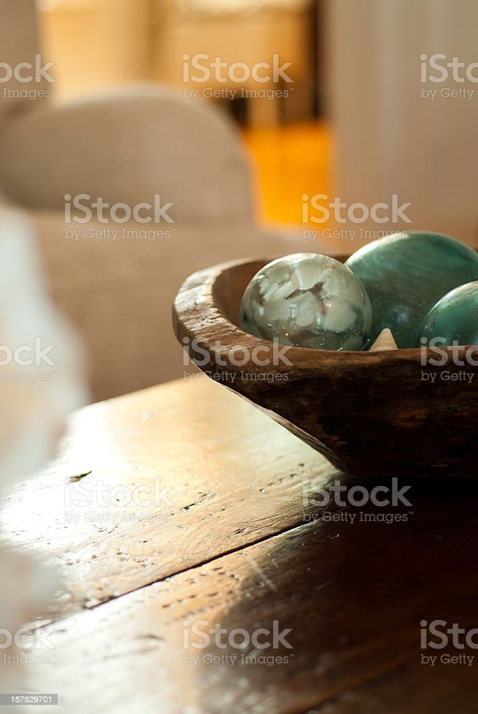 Dark wood coffee table with a bowl of green balls on stock photo