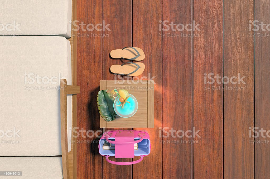 Dark wood decking with a chair, flip flops and drink stock photo