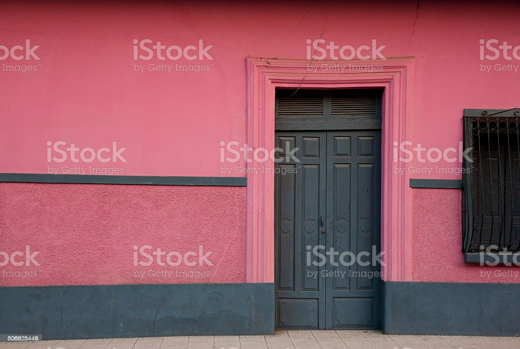 Dark wooden closed door and pink wall stock photo