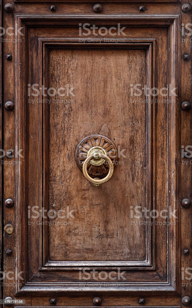 Dark wooden door panel with door knocker. stock photo