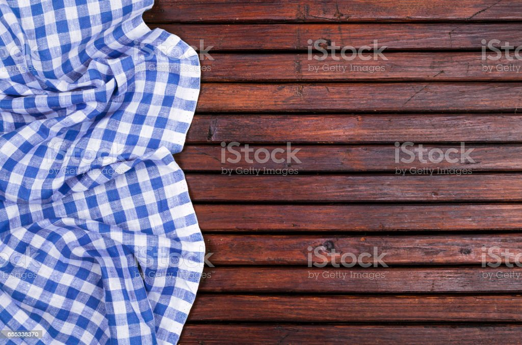 Dark wooden table with blue checkered tablecloth, top view with copy space stock photo