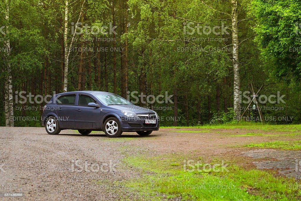 Dark-blue Opel Astra H on a green meadow. Palvaanjarven Campsite stock photo