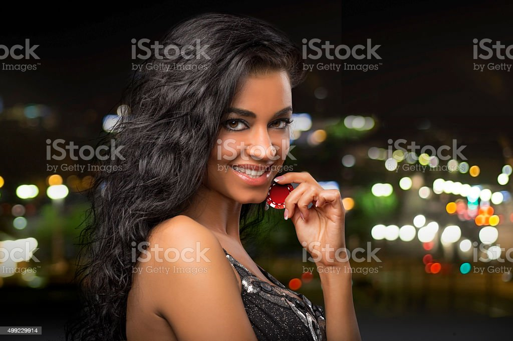dark-haired girl at city background with casino chips stock photo
