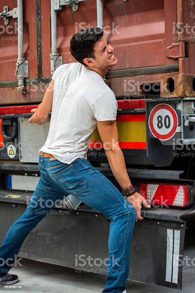 Dark-haired man trying to lift heavy vehicle stock photo