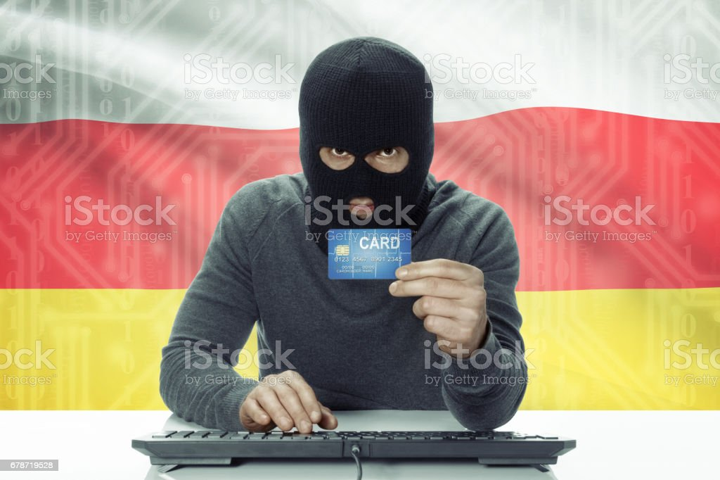 Dark-skinned hacker with flag on background holding credit card - South Ossetia stock photo