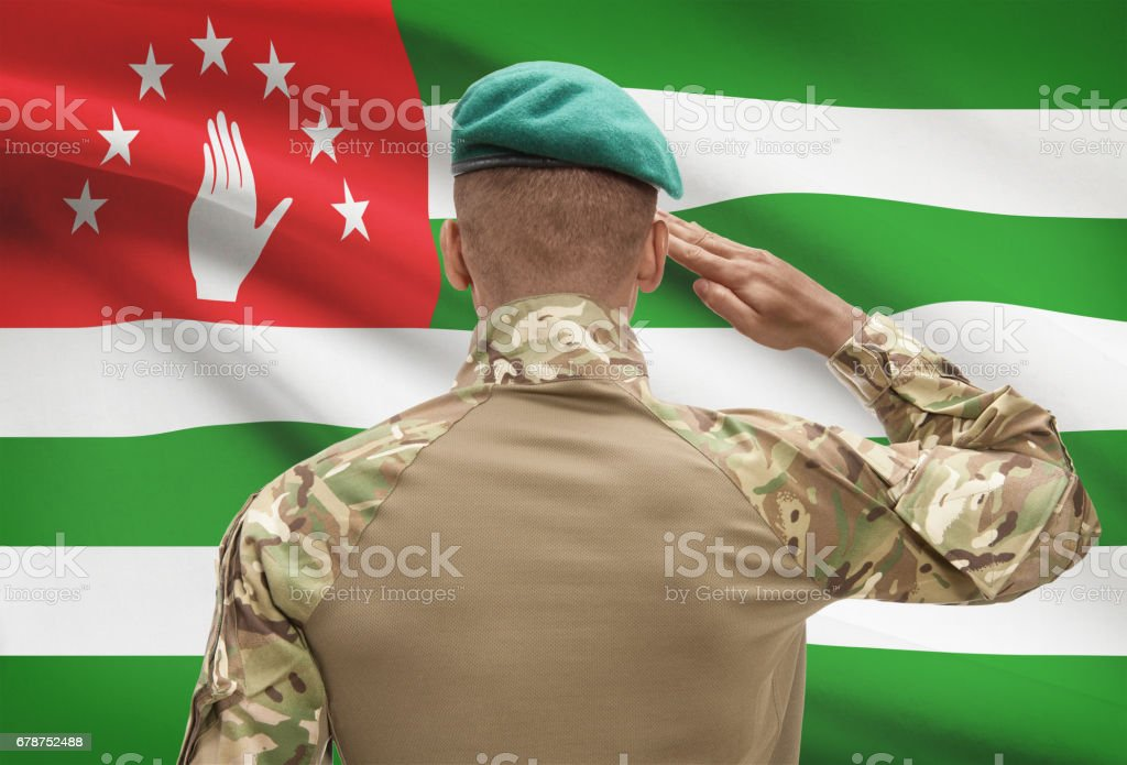 Dark-skinned soldier with flag on background - Abkhazia stock photo