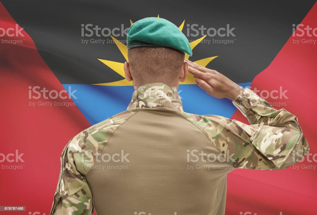 Dark-skinned soldier with flag on background - Antigua and Barbuda stock photo