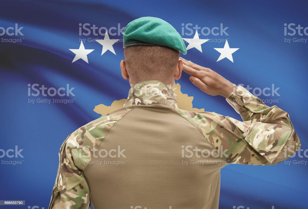 Dark-skinned soldier with flag on background - Kosovo stock photo