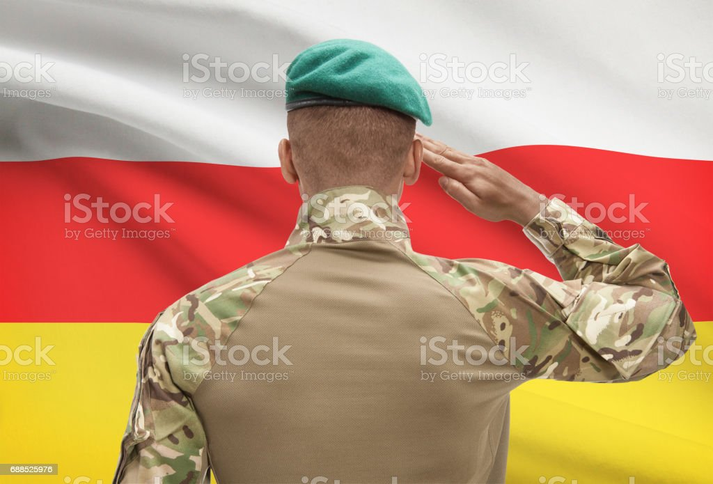 Dark-skinned soldier with flag on background - South Ossetia stock photo