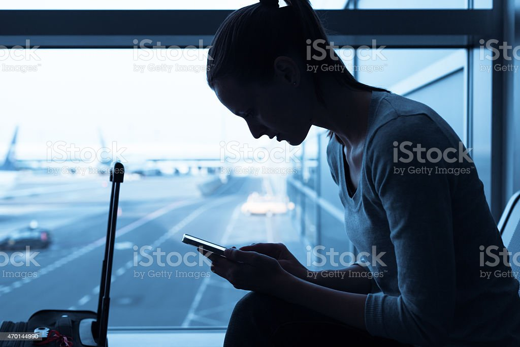 Dark-toned shot of woman using smartphone outside airport stock photo