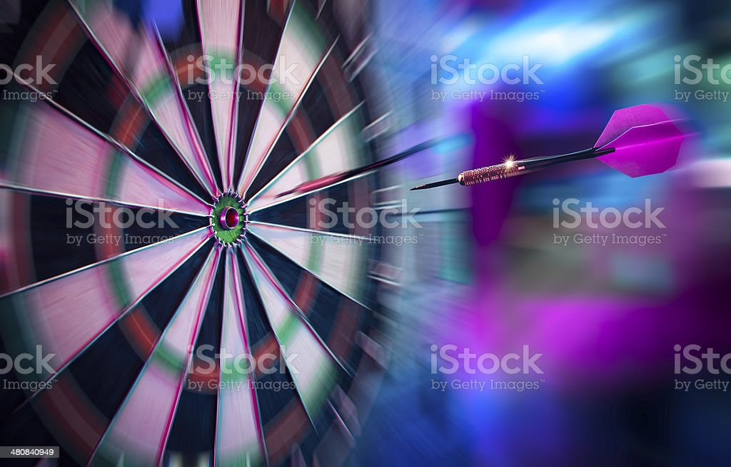 Dart about to hit target with dramatic lighting stock photo