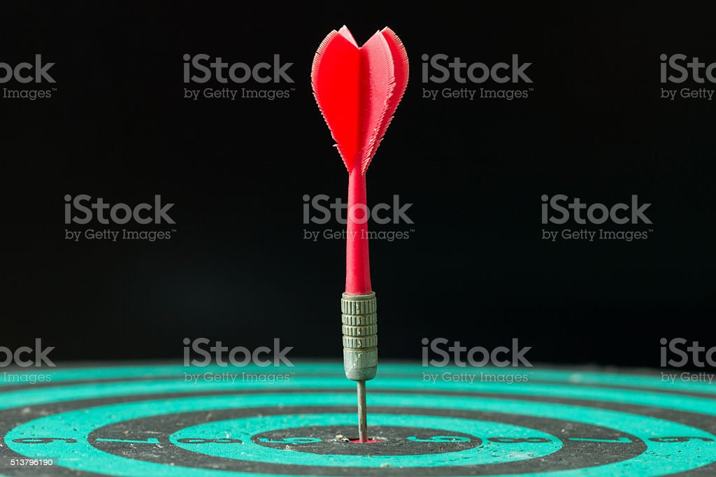 Dart arrow hitting in the center of green dartboard. stock photo