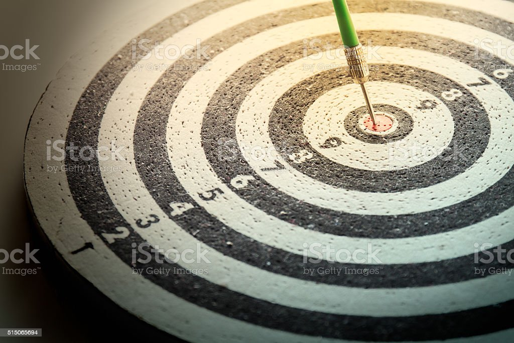 dart arrow hitting in the target center of dartboard, stock photo