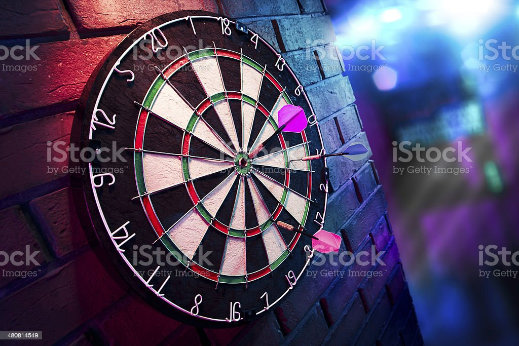 Dart board on a brick wall with dramatic lighting stock photo