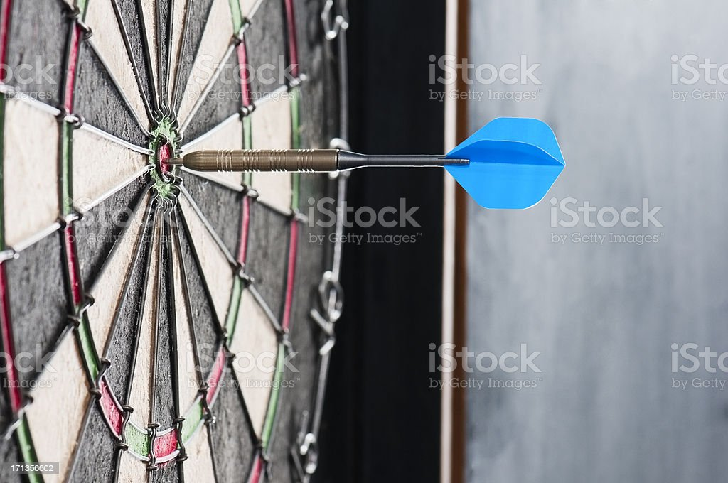 Dart board with a single dart in the bulls eye stock photo