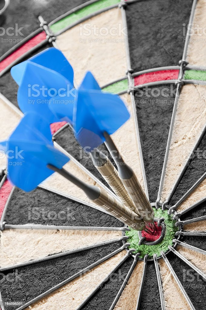 Dart board with three darts in central bull's eye royalty-free stock photo
