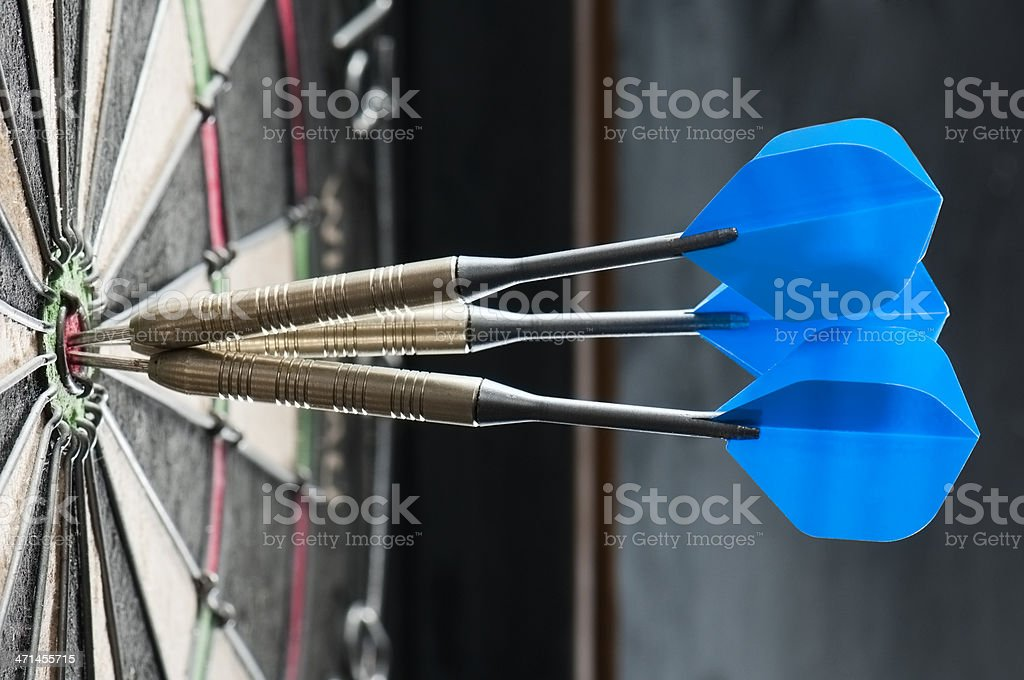 Dart board with three darts in the bulls eye stock photo