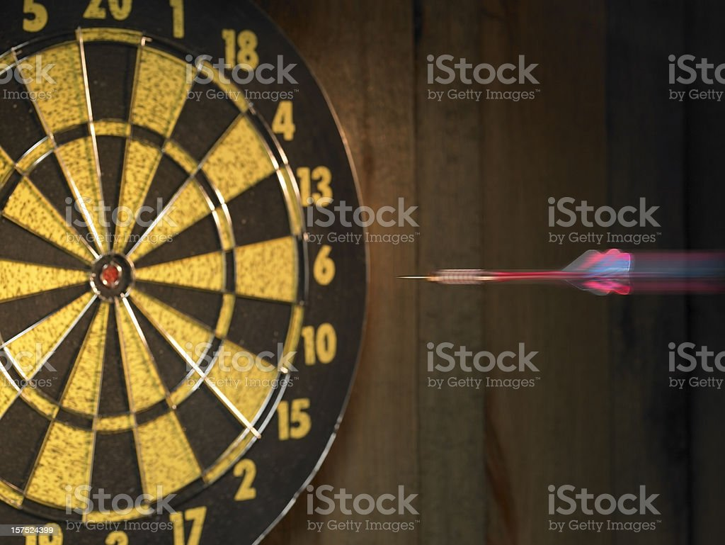 Dart heading for bulls-eye of dartboard royalty-free stock photo