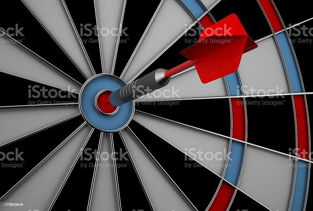 Dart hitting bullseye on dart board stock photo