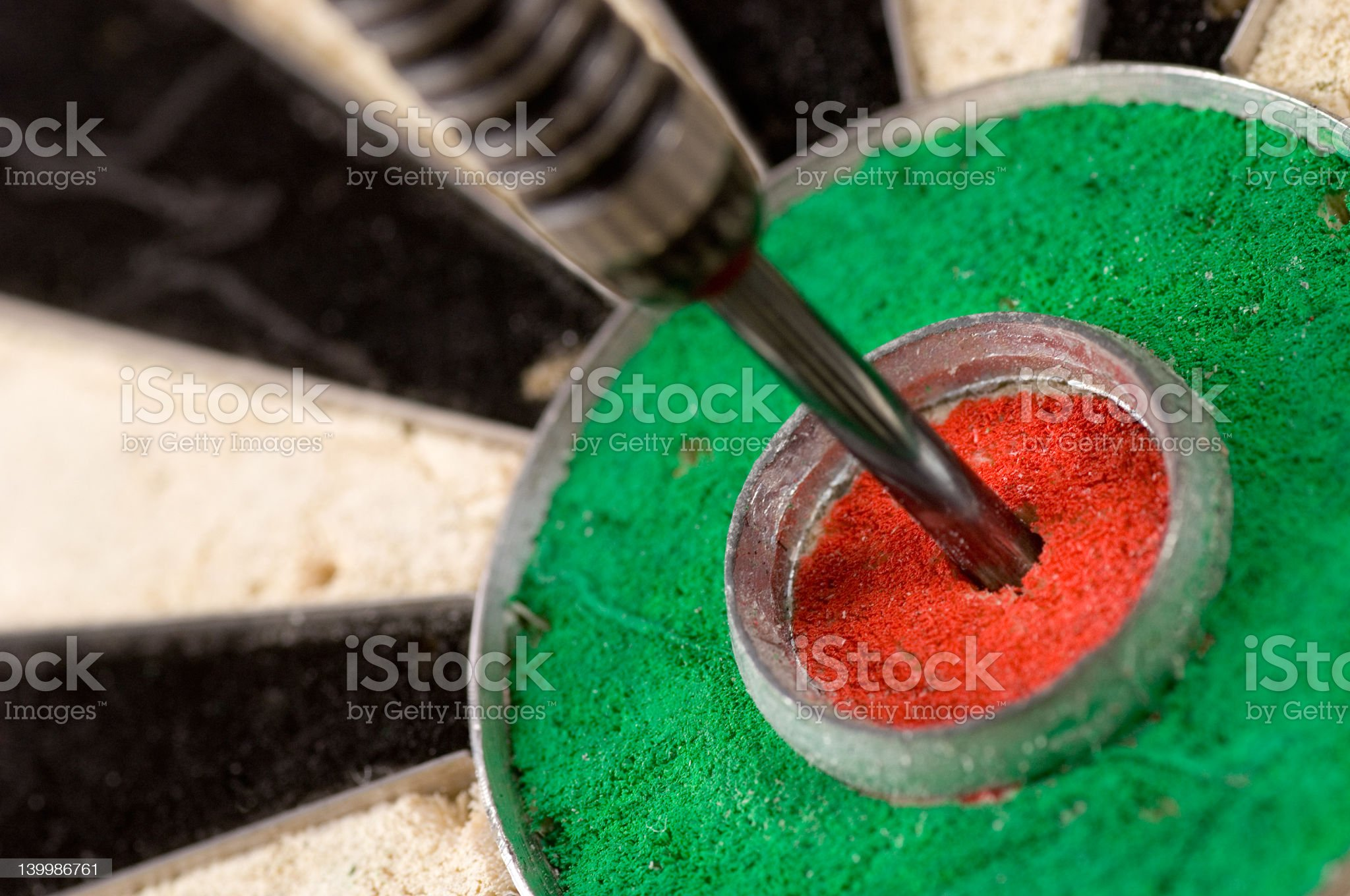 Dart inserted into the center of a dart board, bullseye royalty-free stock photo