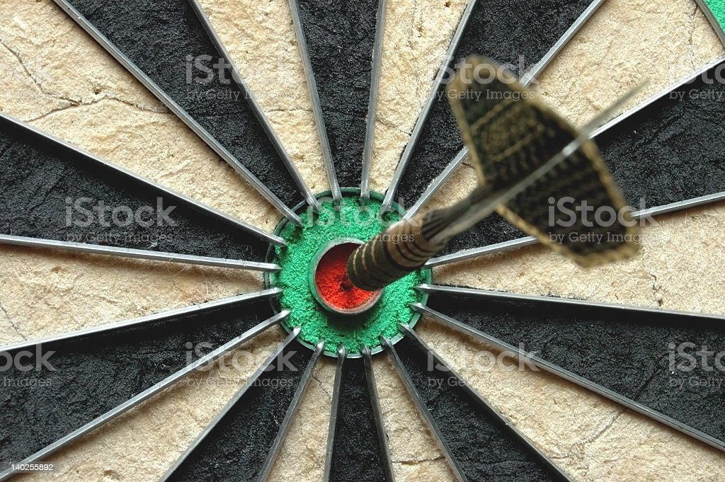 A dart right in the red bullseye stock photo