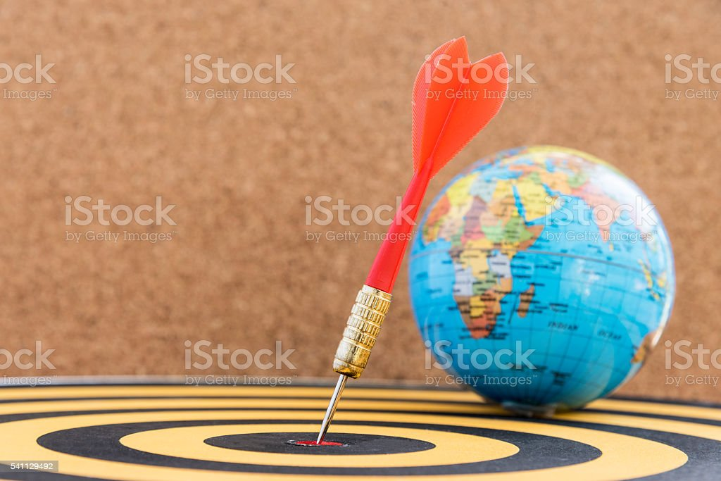 dart target in bullseye on dartboard with globe stock photo