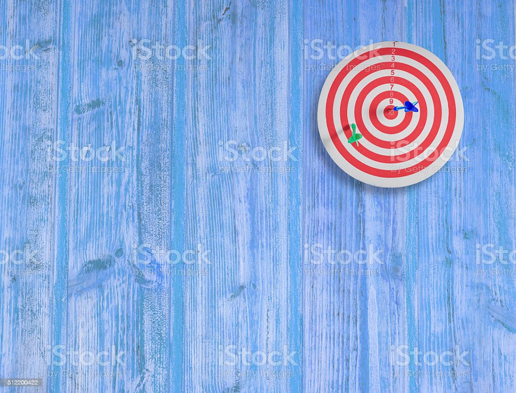 dart target on color wood wall stock photo