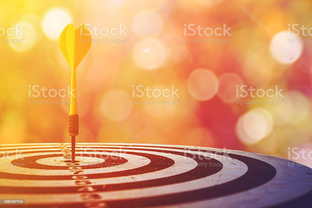 dart target with arrows over bokeh background stock photo