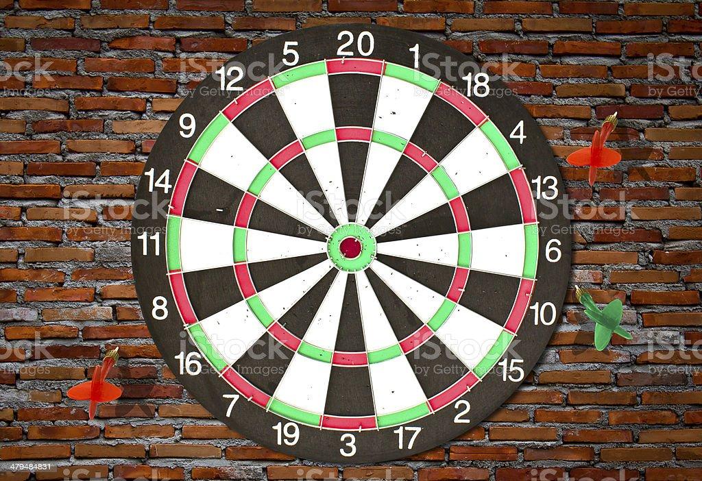 Dartboard on brick wall (Darts Hit Target) stock photo