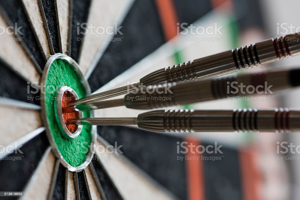 Darts hitting bull's eye on the dartboard stock photo