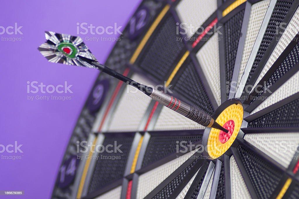 Darts in Bull's eye on Purple royalty-free stock photo
