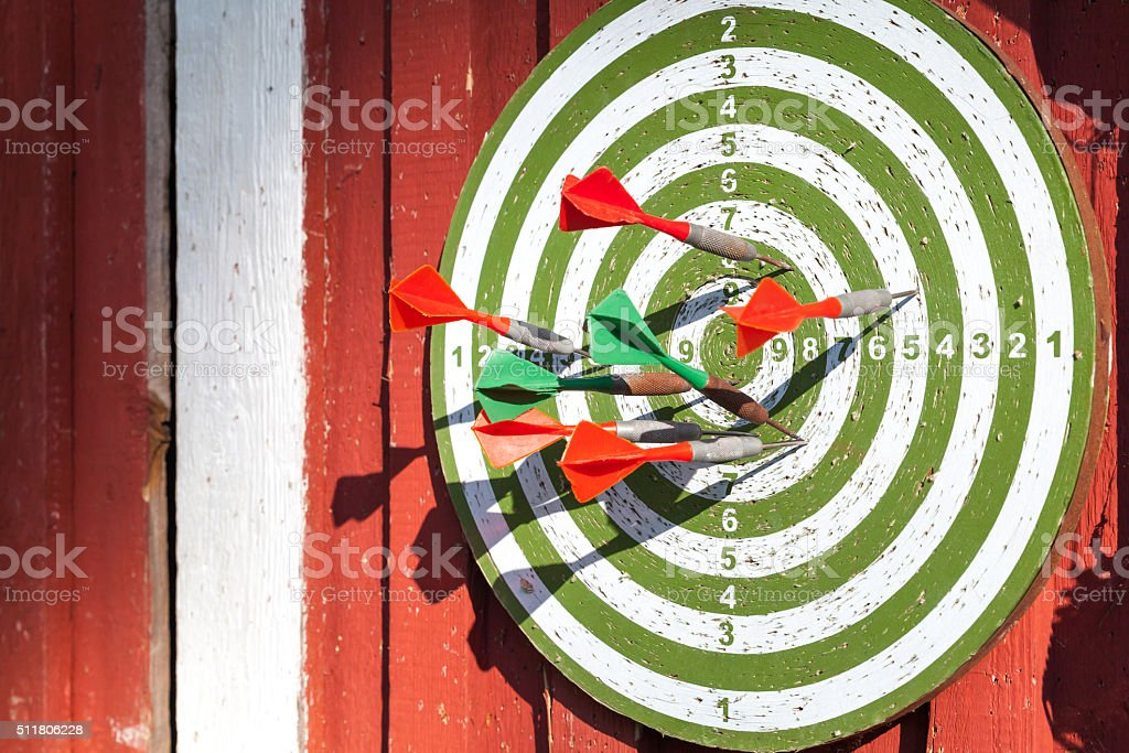 Darts target with many arrows hanging red wooden wall stock photo
