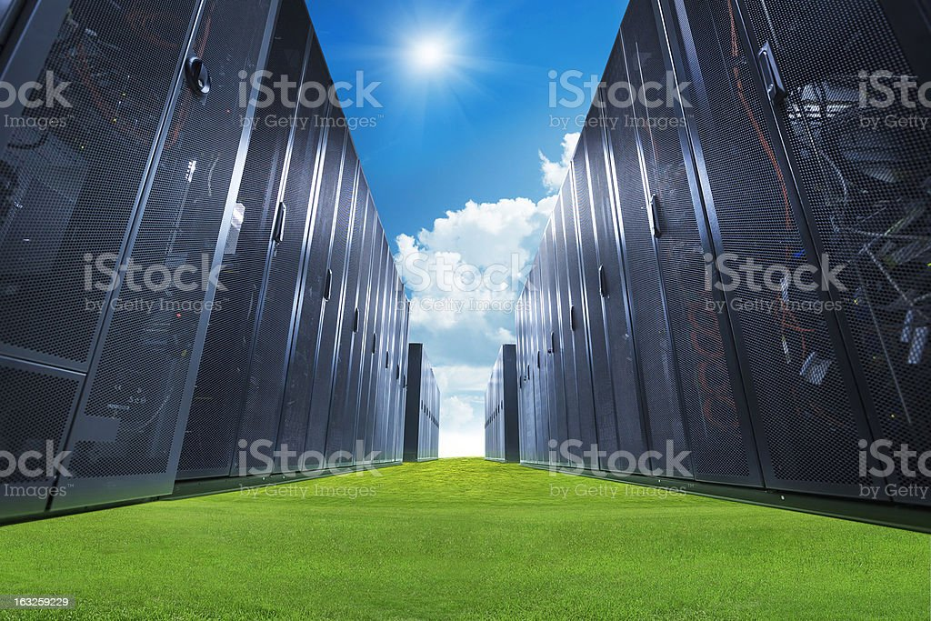 A data center with servers on green grass and a blue sky stock photo