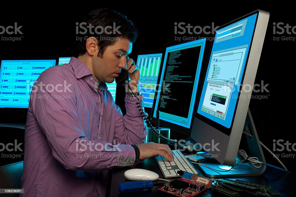 IT Data Manager Phone Support Surrounded by Computer Monitors stock photo