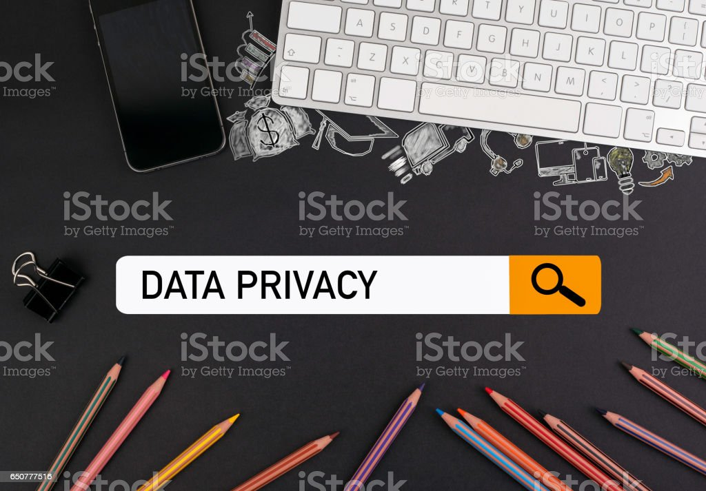 data privacy concept. colorful pencils and a computer keyboard with a mobile phone on a black table stock photo