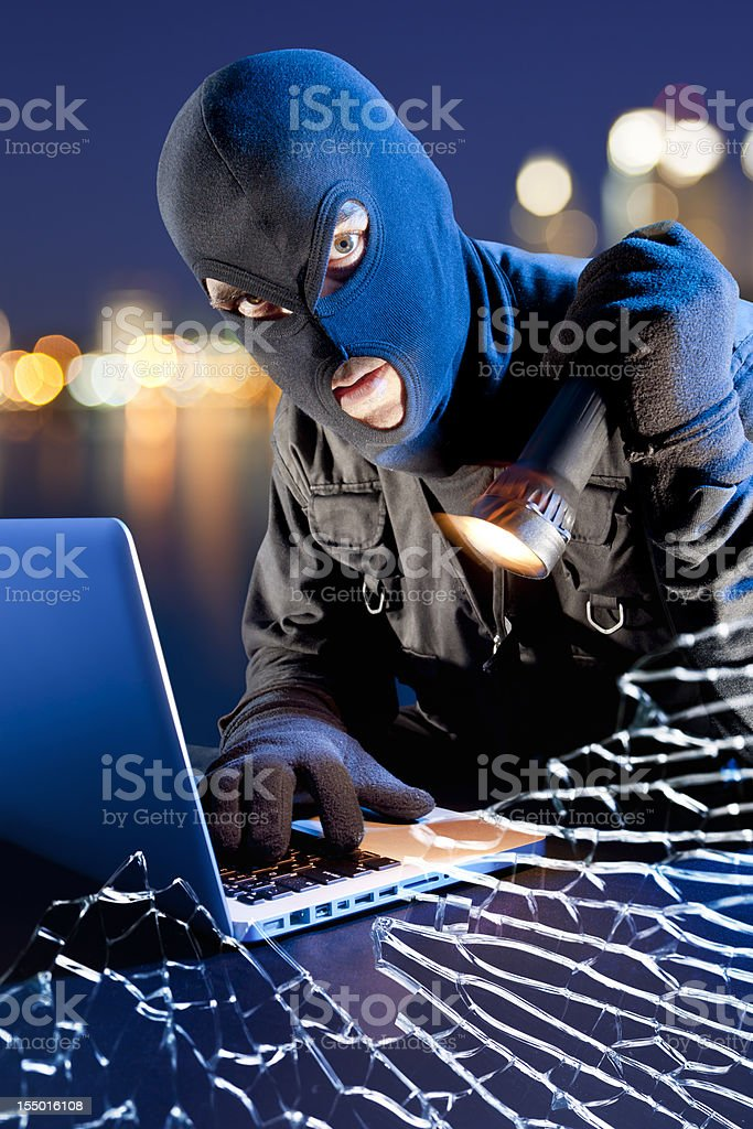 Data thief stealing DVD from laptop behind broken window royalty-free stock photo