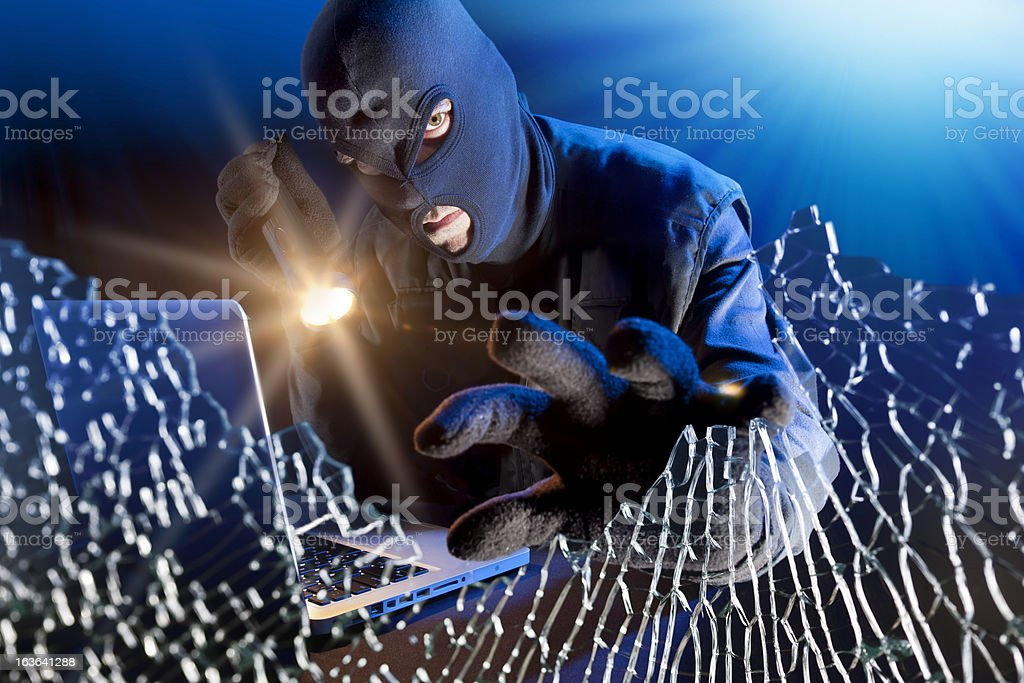 Data thief stealing information from laptop behind broken window royalty-free stock photo