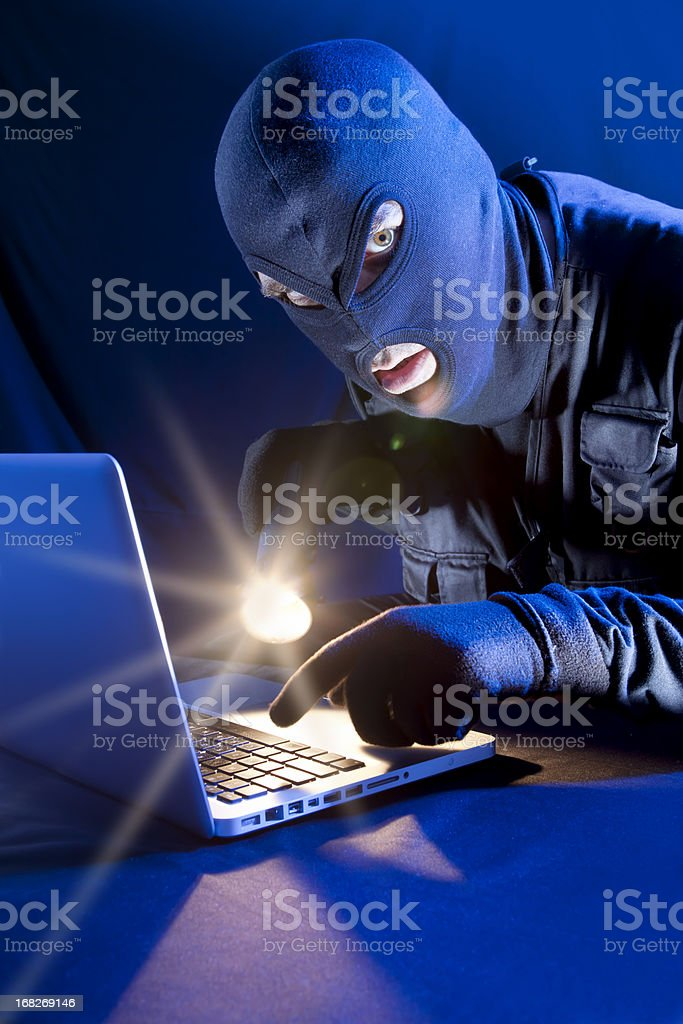 Data thief with flashlight stealing DVD from laptop royalty-free stock photo