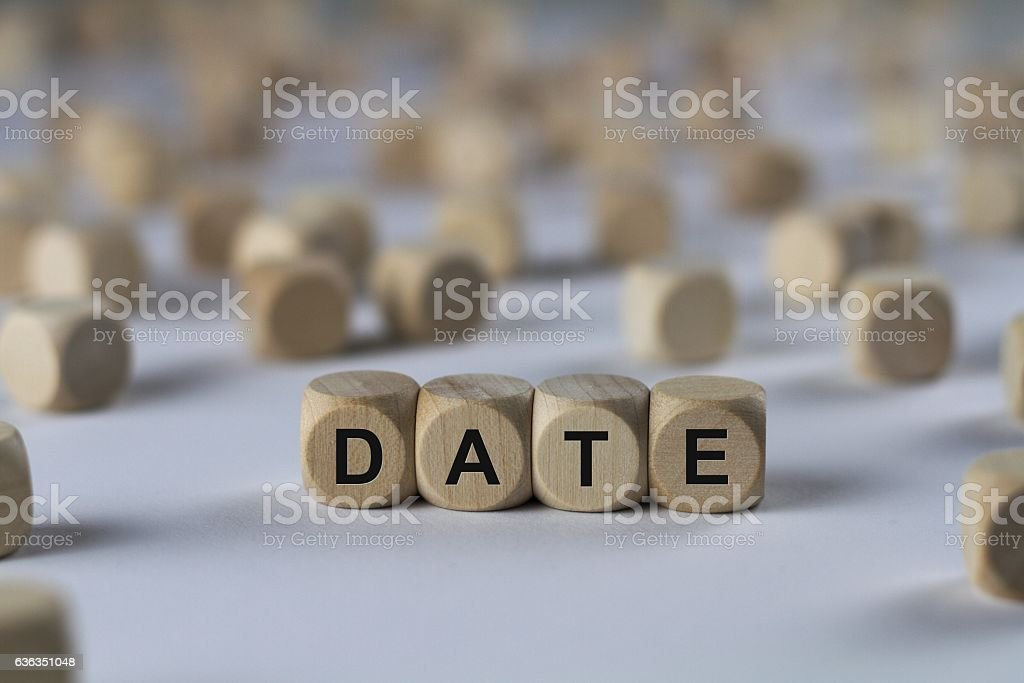 date - cube with letters, sign with wooden cubes stock photo