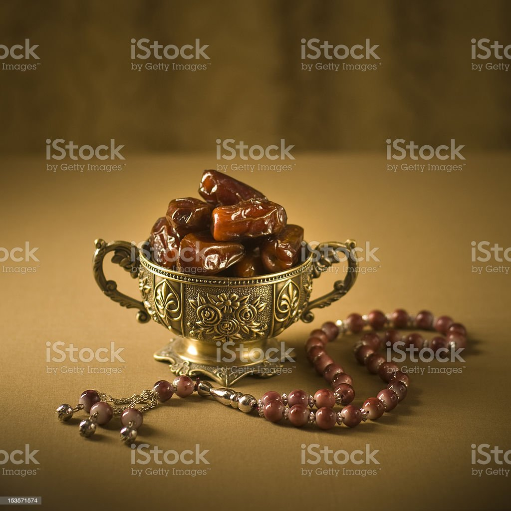 Dates in a small golden goblet with rosary stock photo